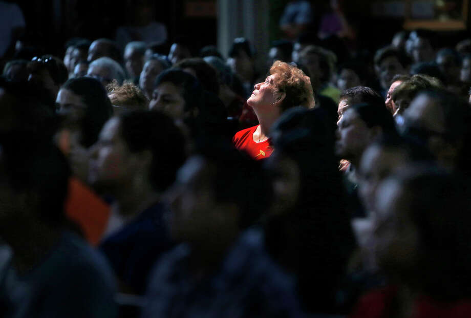 Lupe Mendoza looks up as San Francisco Archbishop Salvatore Cordileone officiates at a Sunday Mass for St. Peter  Catholic Church parishioners who are traveling to Washington, D.C., to see Pope Francis. Photo: Scott Strazzante / Photos By Scott Strazzante / The Chronicle / ONLINE_YES