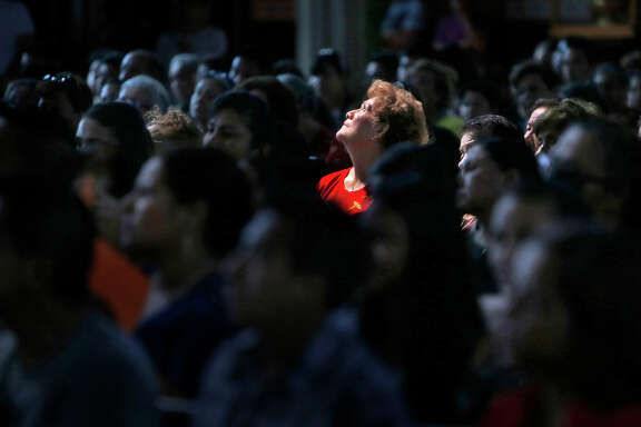 Lupe Mendoza looks up as San Francisco Archbishop Salvatore Cordileone officiates at a Sunday Mass for St. Peter  Catholic Church parishioners who are traveling to Washington, D.C., to see Pope Francis.