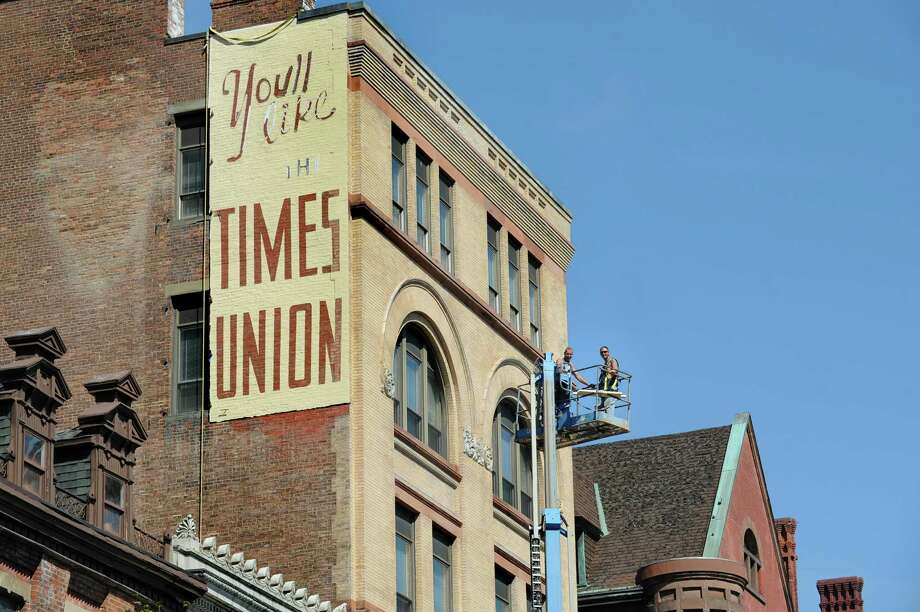 Ed Remillard, left, and Joey Allardice of Jewett Restorations of Saratoga Springs take a break from restoring a Times Union sign at 58 N. Pearl St. on Tuesday, Sept. 15, 2015,  in Albany, N.Y. The historic building will be the Steuben Place Apartments. (Cindy Schultz / Times Union) Photo: Cindy Schultz / 00033370A