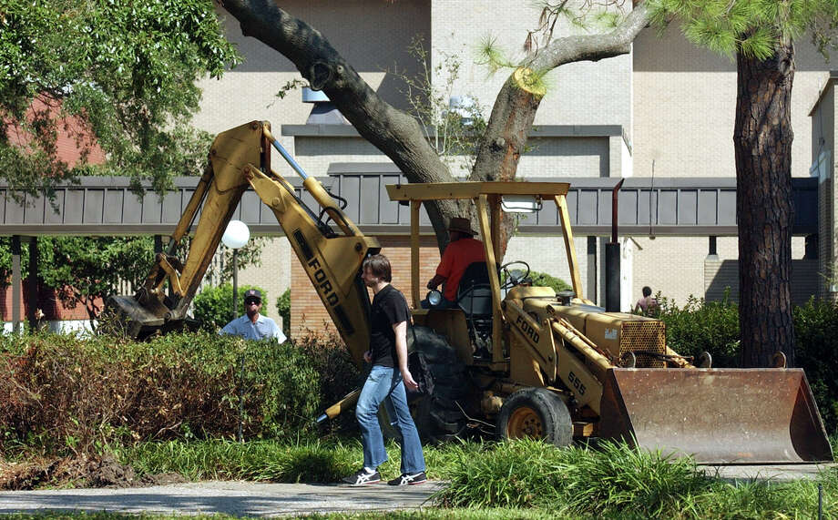 A Lamar University student walks past a maintenance crew cleaning up debris from Hurricane Rita Wednesday on the quad at the school. Students returned for classes on Wednesday after more than three weeks off due to Hurricane Rita. PHOTO/SCOTT ESLINGER                OCT 19, 2005 Photo: SCOTT ESLINGER, STAFF PHOTOGRAPHER / BEAUMONT ENTERPRISE
