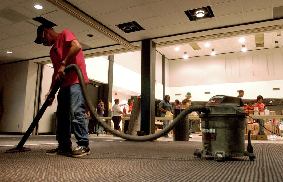 Donald Meaux, 56, of Beaumont, vacuums up debris in the ballroom at the Setzer Student Center on the Lamar University campus as  students, who returned for classes on Wednesday, pick up food items donated by the Red Cross in the ballroom Wednesday afternoon. PHOTO/SCOTT ESLINGER                OCT 19, 2005 Photo: SCOTT ESLINGER, STAFF PHOTOGRAPHER / BEAUMONT ENTERPRISE