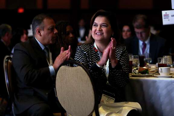 Pricilla Escobar of State Farm applauds Monday while former Florida Gov.  Jeb Bush addresses the U.S. Hispanic Chamber of Commerce. He spoke against Donald Trump on immigrant issues. Story on Page B2.