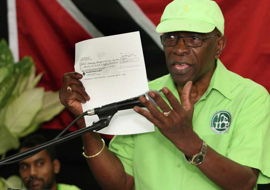 FILE - In this June 3, 2015, file photo, former FIFA vice president Jack Warner hold a copy of a check while he speaks at a political rally in Marabella, Trinidad and Tobago. Trinidad and Tobago's attorney general has signed documents on Monday, Sept. 21, 2015, that pave the way for U.S. extradition proceedings against Warner. The former FIFA vice president is resisting extradition on U.S. charges of racketeering, wire fraud and money laundering in the FIFA corruption case. (Photo/Anthony Harris, File) ORG XMIT: XLAT119 Photo: Anthony Harris / AP