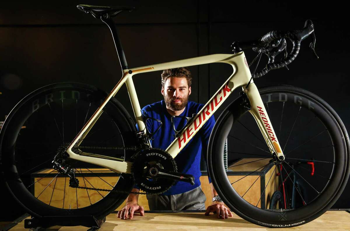 Hedrick Cycles owner and founder Carson Hedrick poses in his new retail shop in Greenwood Friday, Sept. 18, 2015. The white-framed bicycle in front of him will retail for about $12,000 as it is built, but he says his shop will be the highest-end bicycle shop in Seattle, with offerings that will tip the wallet scales at $20,000 or more.