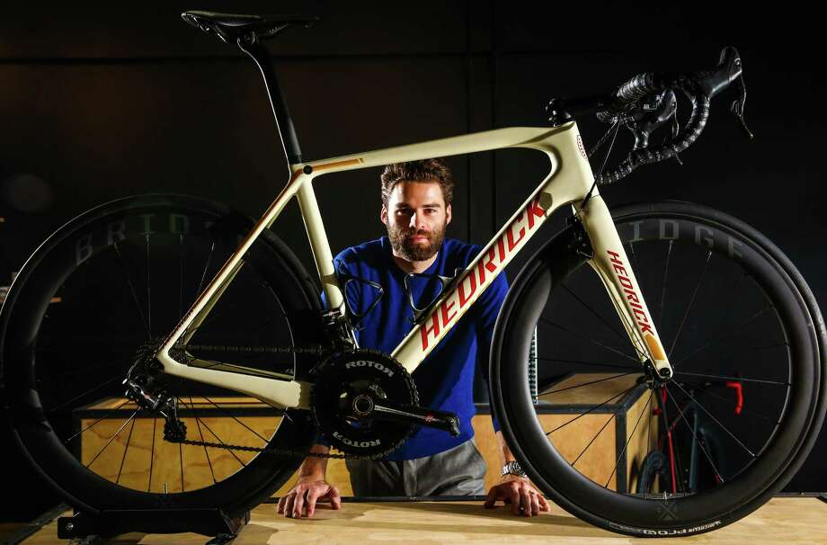 Hedrick Cycles owner and founder Carson Hedrick poses in his new retail shop in Greenwood Friday, Sept. 18, 2015. The white-framed bicycle in front of him will retail for about $12,000 as it is built, but he says his shop will be the highest-end bicycle shop in Seattle, with offerings that will tip the wallet scales at $20,000 or more. Photo: Joshua Trujillo, JOSHUA TRUJILLO/SEATTPI.COM / SEATTLEPI.COM