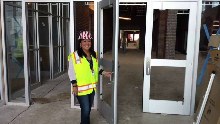 Principal Christy Clark holds open the lobby front door to the still-under-construction Mackey High School, due to open to students in August 2016. Photo: Jeff B. Flinn/ NE Herald / Jeff B. Flinn/ NE Herald
