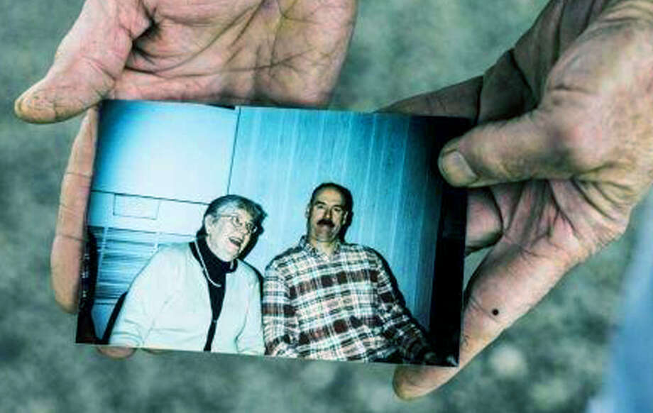 Sam Averill holds a photo of his mother, Jean, and his brother, Mark. Photo: Contributed Photo / The News-Times Contributed