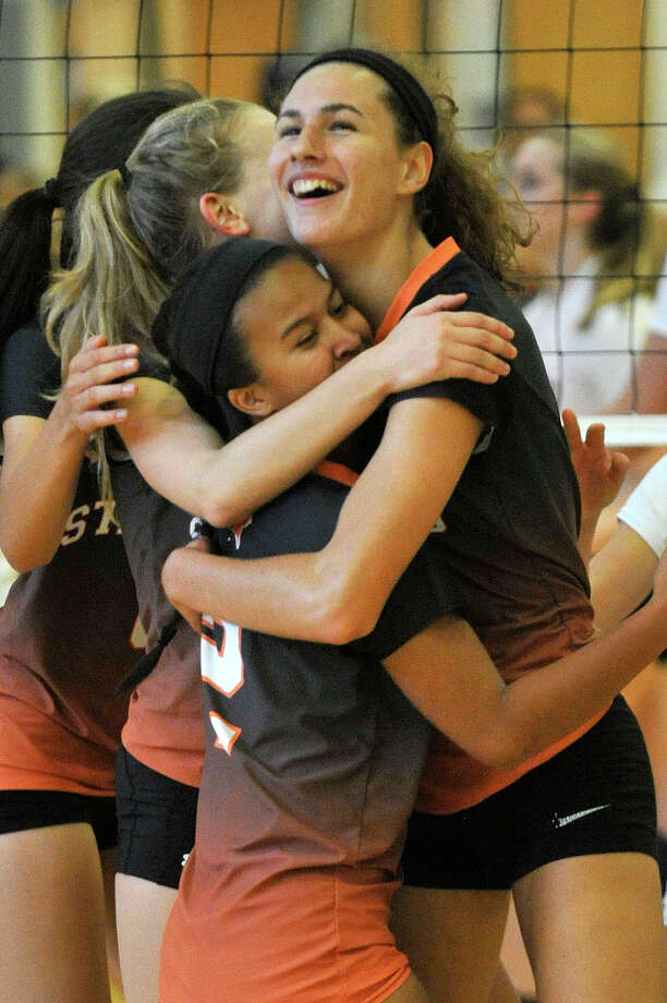 Stamford players from bottom clockwise Camille Martinez, Liisa Balazs and Andrea O'Conner embrace after a point during the Black Knights' volleyball match against New Canaan at Stamford High School in Stamford on Monday. Stamford won, 3-2. Photo: Jason Rearick / Hearst Connecticut Media / Stamford Advocate