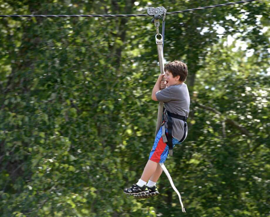 Matthew Cable, 9, of New Milford, takes a ride on the zip line at the New Milford Lions 5tth Annual Country Fair & Car Show, at Harrybrooke Park, in New Milford, Conn, on Saturday, September 19, 2015. Photo: H John Voorhees III / Hearst Connecticut Media / The News-Times