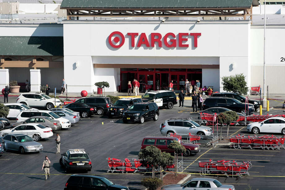 Police taped off a section of the parking lot of a Target store after a fatal shooting Monday, Sept. 21, 2015, in Sand City, Calif. Monterey District Attorney Dean Flippo tells the Santa Cruz Sentinel officers were trying to serve a warrant to men sitting in a car at the store when the gun fight broke out. (Vern Fisher/The Monterey County Herald via AP) MANDATORY CREDIT Photo: Vern Fisher / Associated Press / The Monterey County Herald