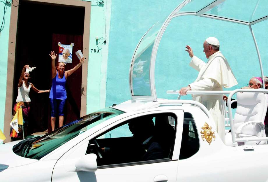 Pope Francis waves at people lined up along his way in Holguin, eastern Cuba, on September 21, 2015. Holguin, a cradle of Catholic faith on the island and also the home region of communist leaders Fidel and Raul Castro, is the only stop on the pope's eight-day, six-city tour of Cuba and the United States that has never received a papal visit. AFP PHOTO/BALTAZAR MESABALTAZAR MESA/AFP/Getty Images Photo: BALTAZAR MESA / AFP