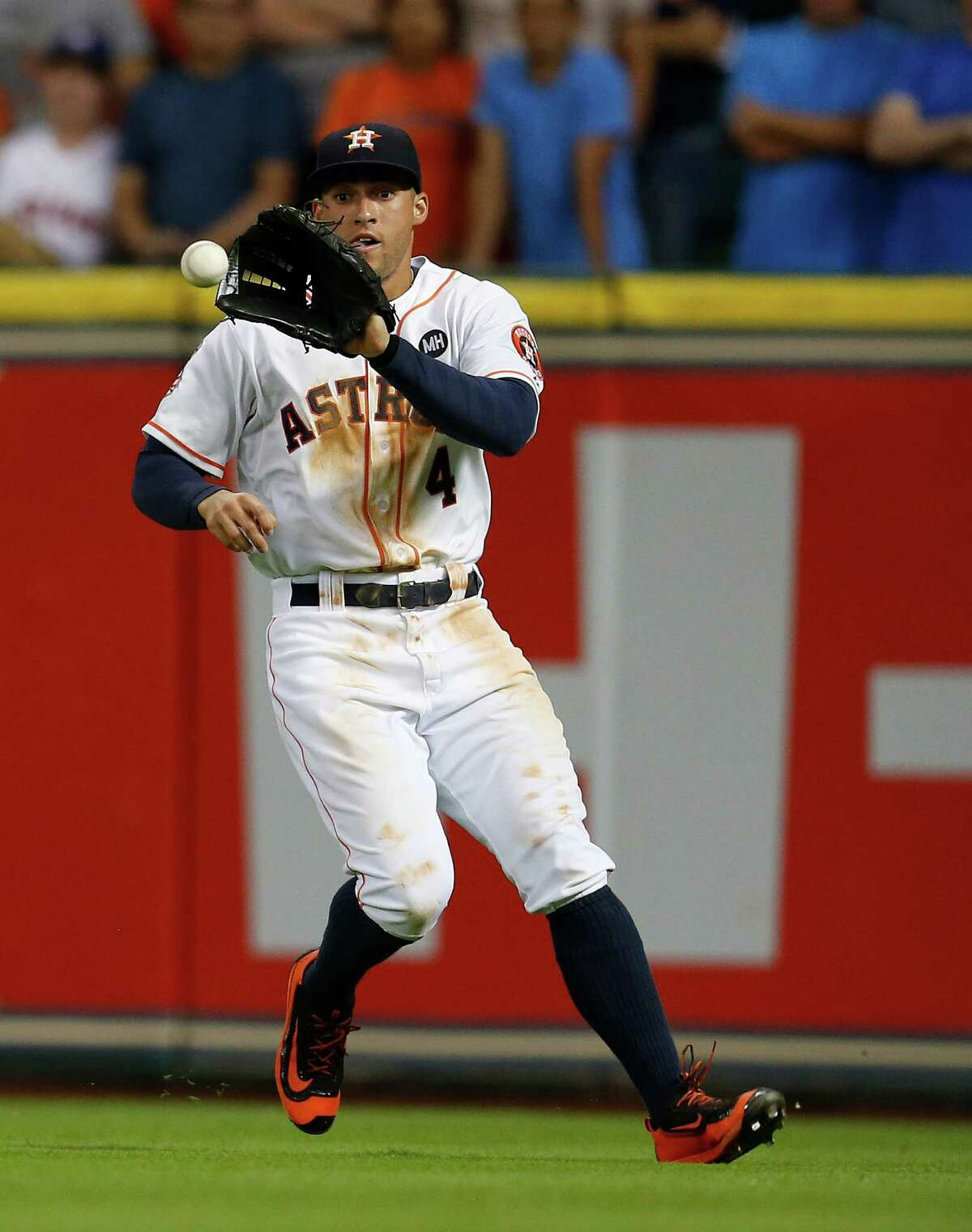 Houston Astros right fielder George Springer (4) tries to make a catch on Los Angeles Angels left fielder Collin Cowgill's line drive during the ninth inning of an MLB game at Minute Maid Park on Monday, Sept. 21, 2015.