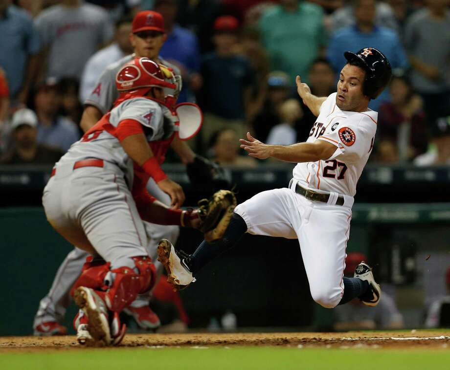 Astros second baseman Jose Altuve slides home but fails to avoid the tag of Angels catcher Carlos Perez in the fifth inning. Photo: Karen Warren, Staff / © 2015 Houston Chronicle