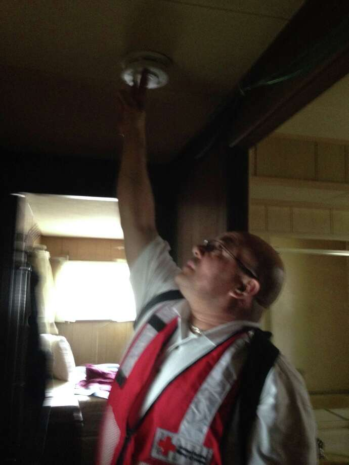 A volunteer from the American Red Cross installs a smoke detector in one of Shelton's mobile homes during a recent fire safety campaign with the Shelton Fire Department. Photo: Shelton Fire Department Photo