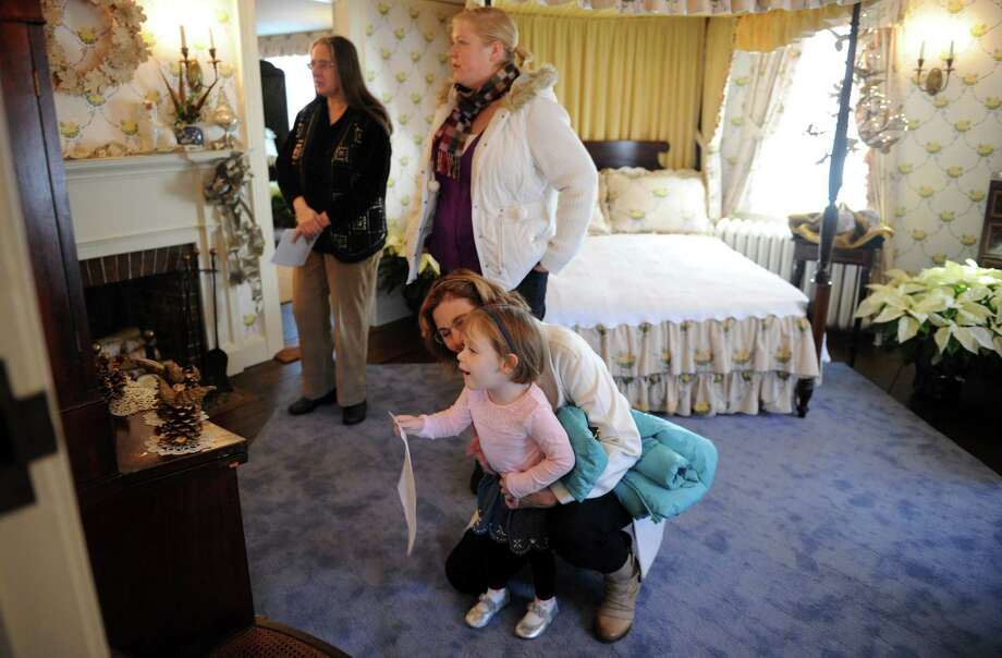 Historical interpreter Patricia Sweeney, far left, leads 3-year-old Charlotte Chenery, of Derby, and her mother Heather and grandmother Kim Chenery on a tour of the Osborne Homestead Museum in Derby, Conn. Friday, Nov. 28, 2014. This year's holiday decor at the former home of Frances Osborne Kellogg is inspired by the symphony orchestra, with 10 rooms each showcasing different musical components.  Holiday museum tours run Thursday to Sunday through December 20th, from 10 a.m. to 4 p.m.  Admission is free and donations are accepted. Photo: Autumn Driscoll / Autumn Driscoll / Connecticut Post