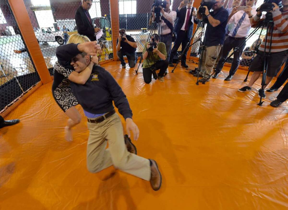 Assemblyman Angelo Santabarbara, D-Rotterdam, is taken to the mat by a mother of three during a demonstration of mixed martial arts at the Schenectady Armory on Washington Avenue. The armory will host an amateur MMA card on Saturday. (Skip Dickstein / Times Union)