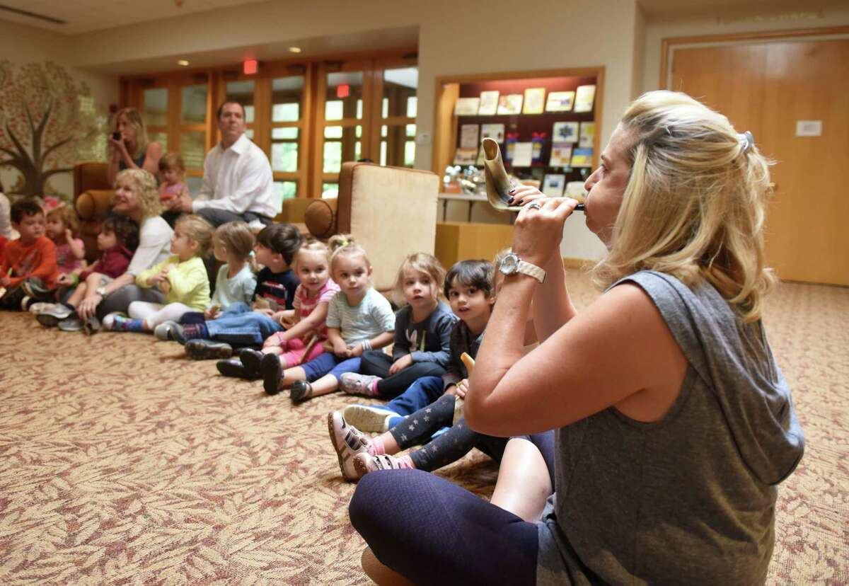 Three-year-old teacher Lisa Levine blows a shofar at Temple Sholom in Greenwich, Conn. Tuesday, Sept. 22, 2015. The shofar is an istrument typically made from a ram's horn that is blown ceremonially at Rosh Hashanah, which was last Tuesday and Wednesday, and Yom Kippur, which is this Wednesday. The nursery children were taught how the shofar was used historically, how it's used in present-day synagogue services and, of course, how to blow the horn.
