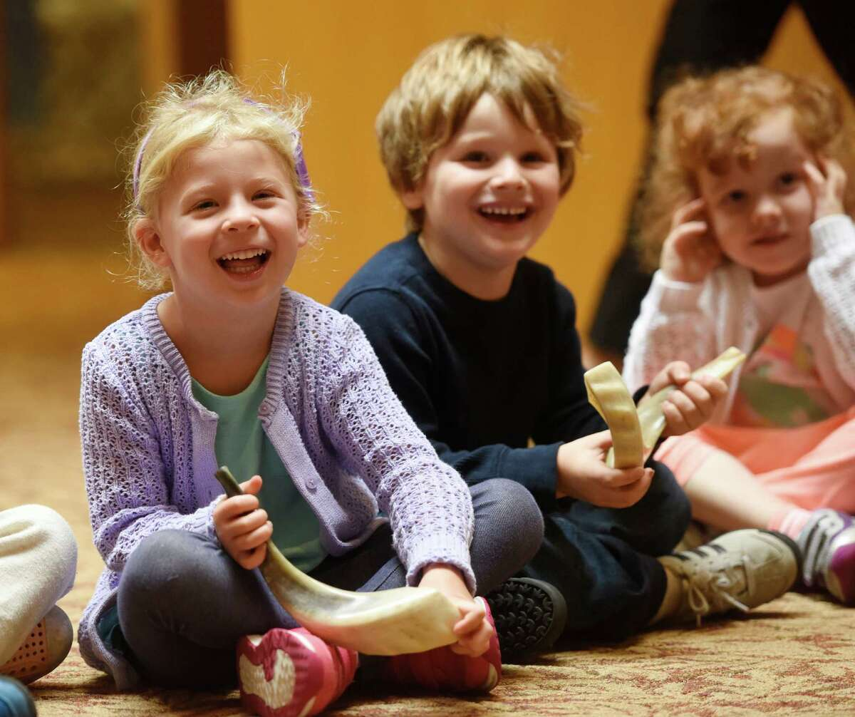 Four-year-olds Addy Schamberg, left, Brandon Zwilling and Sophia Barrocas react to the loud noise of a shofar at Temple Sholom in Greenwich, Conn. Tuesday, Sept. 22, 2015. The shofar is an istrument typically made from a ram's horn that is blown ceremonially at Rosh Hashanah, which was last Tuesday and Wednesday, and Yom Kippur, which is this Wednesday. The nursery children were taught how the shofar was used historically, how it's used in present-day synagogue services and, of course, how to blow the horn.