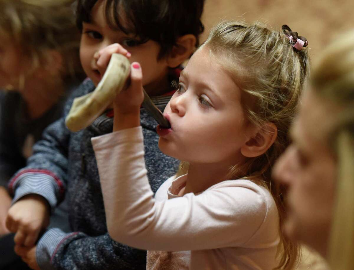 Emma Gibson, 3, blows a shofar at Temple Sholom in Greenwich, Conn. Tuesday, Sept. 22, 2015. The shofar is an istrument typically made from a ram's horn that is blown ceremonially at Rosh Hashanah, which was last Tuesday and Wednesday, and Yom Kippur, which is this Wednesday. The nursery children were taught how the shofar was used historically, how it's used in present-day synagogue services and, of course, how to blow the horn.
