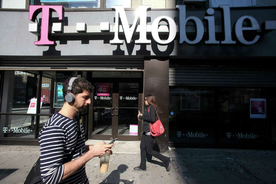 In this Sept. 12, 2012 file photo, a man uses a cellphone as he passes a T-Mobile store in New York. (AP Photo/Mark Lennihan, File) Photo: Mark Lennihan, STF / AP