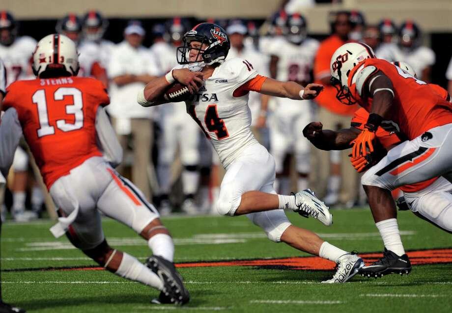 UTSA quarterback Dalton Sturm runs between Oklahoma State defenders safety Jordan Sterns (13) and linebacker Devane Averette on Sept. 19, 2015. Photo: Brody Schmidt /Associated Press / FR79308 AP