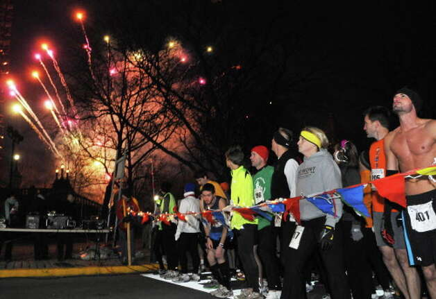 Runners stand at the ready as fireworks mark  the start of the 15th Annual Last Run 5K  race in Albany Saturday Dec. 17, 2011.    (John Carl D'Annibale / Times Union) Photo: John Carl D'Annibale / 00015785A