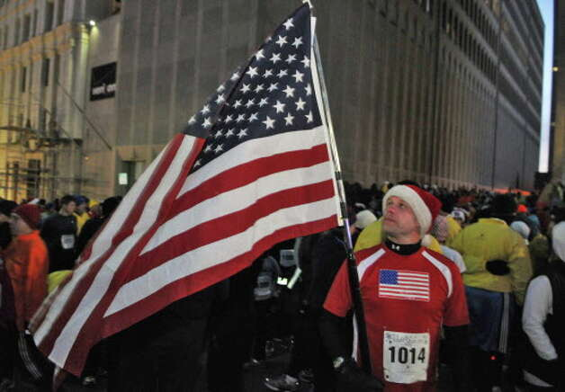 """""""Miles 4 Vets"""" runner Robert Smith of East Berne unfurls an American flag at the start of the 15th Annual Last Run 5K  race in Albany Saturday Dec. 17, 2011.    (John Carl D'Annibale / Times Union) Photo: John Carl D'Annibale / 00015785A"""