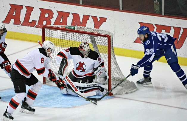 Syracuse Crunch's #33 Dalton Smith, right, has his shot stopped by Albany Devils's #8 Dan Kelly, left, and goalie Scott Wedgewood during Saturday's game at the Times Union Center  March 14, 2015 in Albany, NY.  (John Carl D'Annibale / Times Union) Photo: John Carl D'Annibale / 00030124L