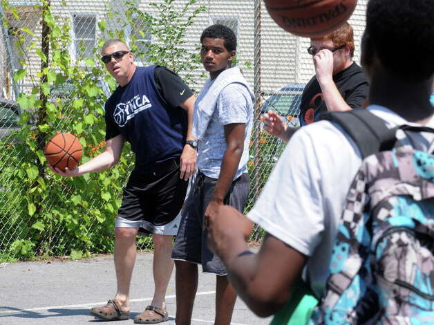 Schenectady Police Chief Brian Kilcullen, left, warms up with other players during the Schenectady community police basketball game at Jerry Burrell Park on Saturday July 11, 2015 in Schenectady, N.Y. (Michael P. Farrell/Times Union) Photo: Michael P. Farrell / 00032579A
