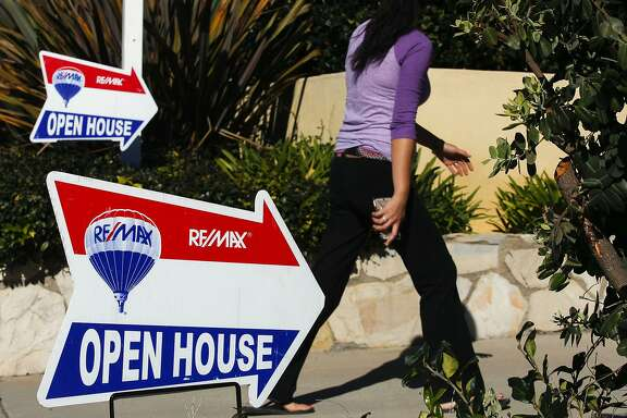 A woman walks past RE/MAX Holdings Inc. signage while arriving for an open house in Redondo Beach, California, U.S., on Saturday, Feb. 14, 2015. The National Association of Realtors is scheduled to release existing home sales figures on Feb. 23. Photographer: Patrick T. Fallon/Bloomberg