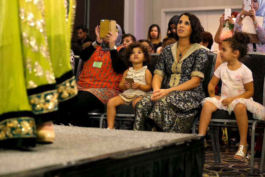 Meriem Hassan (center) and her daughters 2-year-old Noor Hassan (left) and 4-year-old Melek Hassan keep an eye on the runway. Photo: Connor Radnovich, The Chronicle