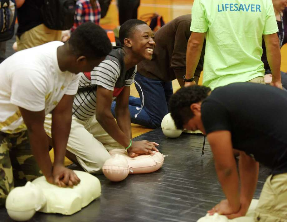 Stamford junior Theslyn Tide performs chest compressions during the Hands for Life CPR training event at Stamford High School in Stamford, Conn. Tuesday, Sept. 22, 2015.  More than 1,800 students were trained at the high school Tuesday with assistance by 52 trainers from Stamford Hospital, Health Department, Fire Department and other local groups.  Training will continue at Trinity Catholic High School Wednesday, Turn of River and Scofield Middle Schools Thursday, Westhill High School Friday, and a public session at Westhill High School on Saturday.  The program's goal is to train 10,000 people in compression-only CPR and spread awareness that everybody should be trained. Photo: Tyler Sizemore / Hearst Connecticut Media / Greenwich Time