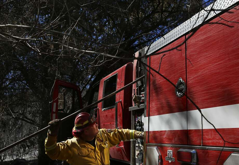 Fire Captain Kevin Bowman feeds a water hose to his crew as they put out hot spots during the Tassajara Fire Sept. 22, 2015 in Monterey County, Calif. As of Tuesday morning the fire had destroyed 18 structures, killed one person and was at 65% containment. Photo: Leah Millis, The Chronicle