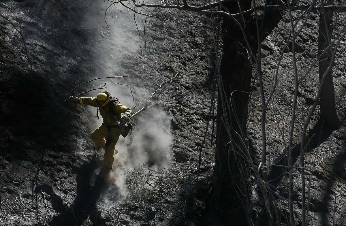 Xavier Lugo of Cal Fire's Mariposa unit scurries down a steep, ashy slope after working with his crew to put out hot spots during the Tassajara Fire Sept. 22, 2015 in Monterey County, Calif. As of Tuesday morning the fire had destroyed 18 structures, killed one person and was at 65% containment.