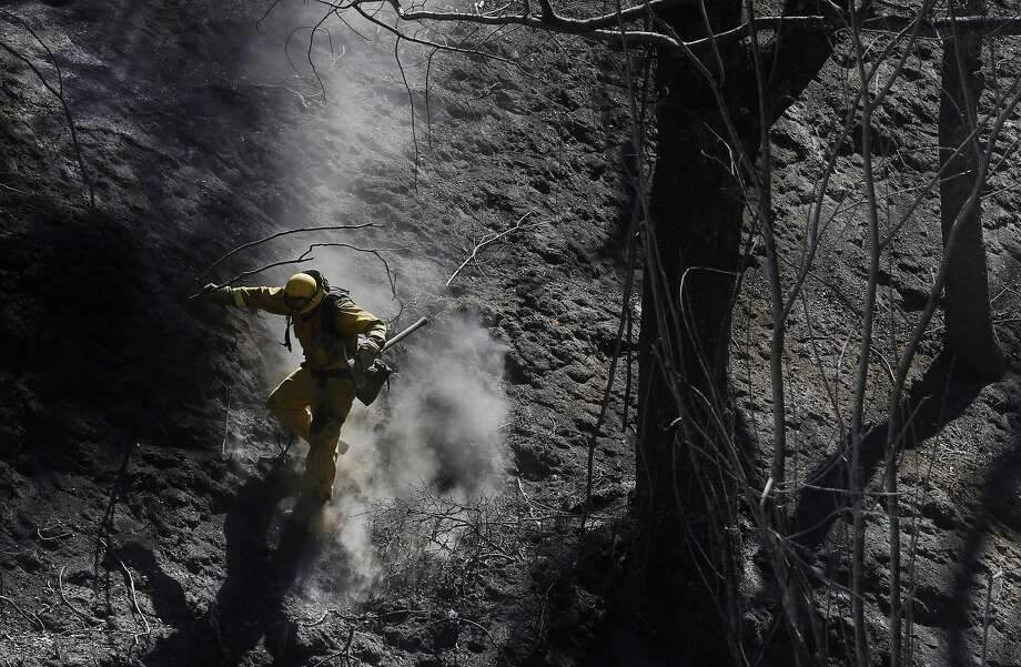 Xavier Lugo of Cal Fire's Mariposa unit scurries down a steep, ashy slope after working with his crew to put out hot spots during the Tassajara Fire Sept. 22, 2015 in Monterey County, Calif. As of Tuesday morning the fire had destroyed 18 structures, killed one person and was at 65% containment. Photo: Leah Millis, The Chronicle