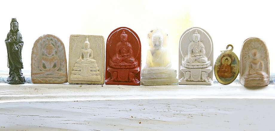 Writer Dana Velden shows her miniature buddhas on the window sill over the kitchen sink in her Oakland home. Photo: Liz Hafalia, The Chronicle