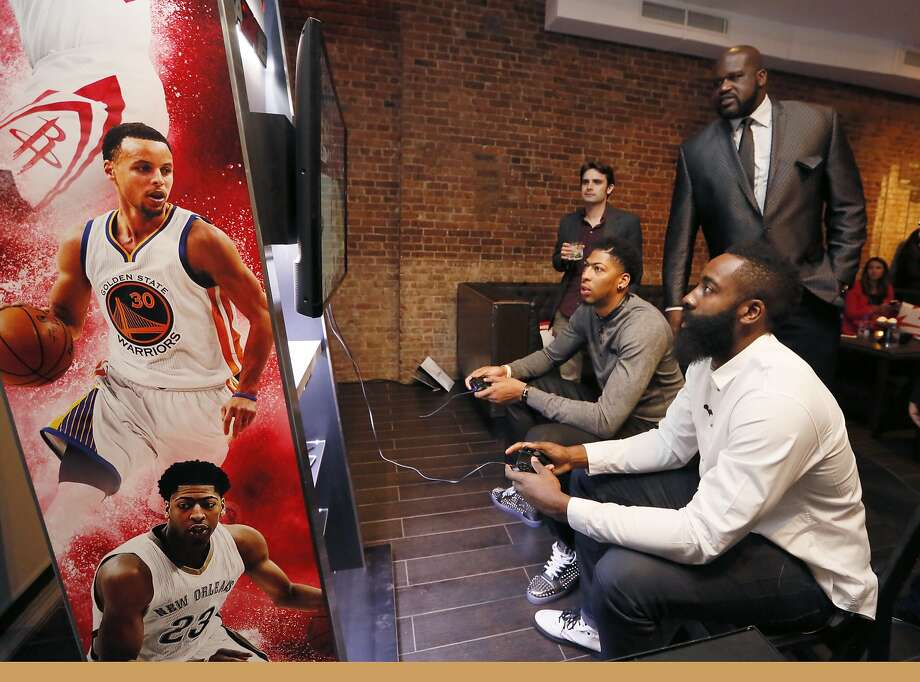 Shaquille O'Neal, right, looks on as Anthony Davis, left, and James Harden play NBA 2K16 at Monday's premiere. Photo: Stuart Ramson, Associated Press