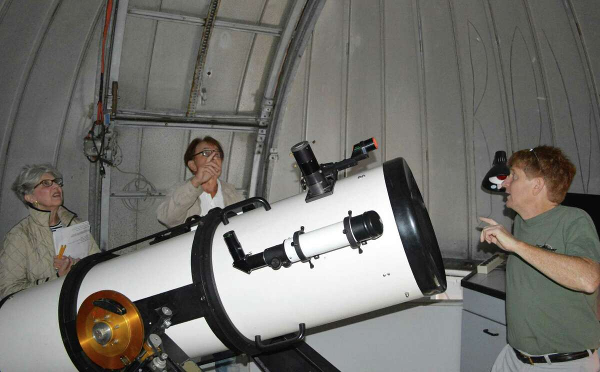 Kevin Green of the Westport Astronomical Society, which has based its Rolnick Observatory in one of the former Nike missle radar towers on Bayberry Lane, shows off its telecope under the dome to Carol Leahy and Don Bergman during a Tuesday tour of the facilities.