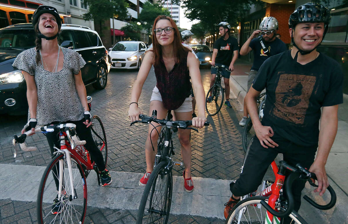 Lisa Hood (from left), Bike World employee Abigail McMains, Elijah Echeveste, and others stop at a red light during a Thursday night social bike ride through downtown in July.