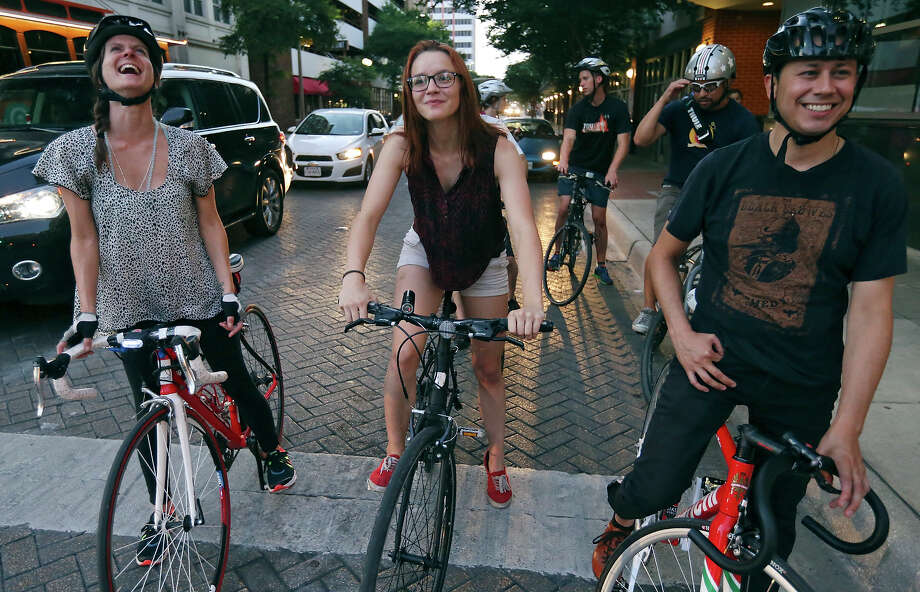 Lisa Hood (from left), Bike World employee Abigail McMains, Elijah Echeveste, and others stop at a red light during a Thursday night social bike ride through downtown in July. Photo: Edward A. Ornelas /San Antonio Express-News / © 2015 San Antonio Express-News