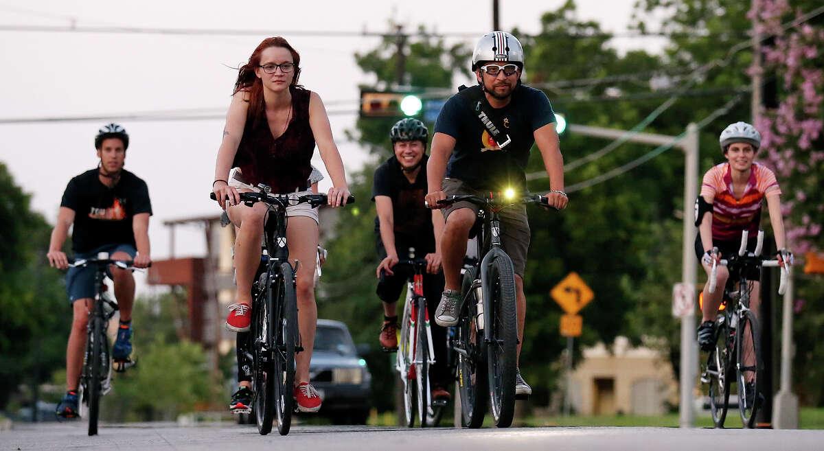 Brett Shudak (from left), Bike World employee Abigail McMains, Elijah Echeveste, Bike World employee Eddie Martinez, and Courtney Haass pedal through downtown during a social ride in July.
