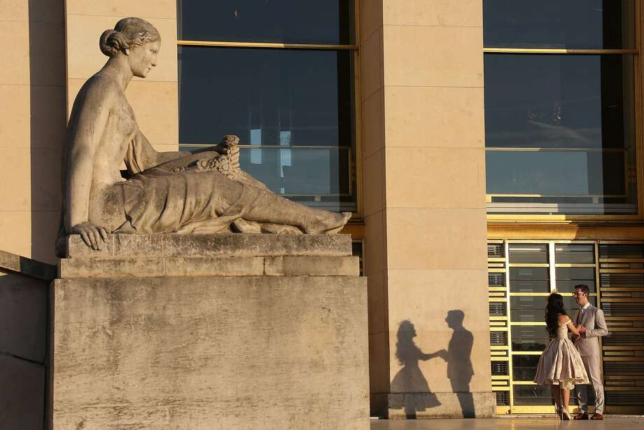 A couple stands on the Esplanade du Trocadero  at sunrise, in front of Chaillot palace, next to Flore statue from Olivier Lejeune (1837) on september 21, 2015, in Paris. Photo: Ludovic Marin, AFP / Getty Images