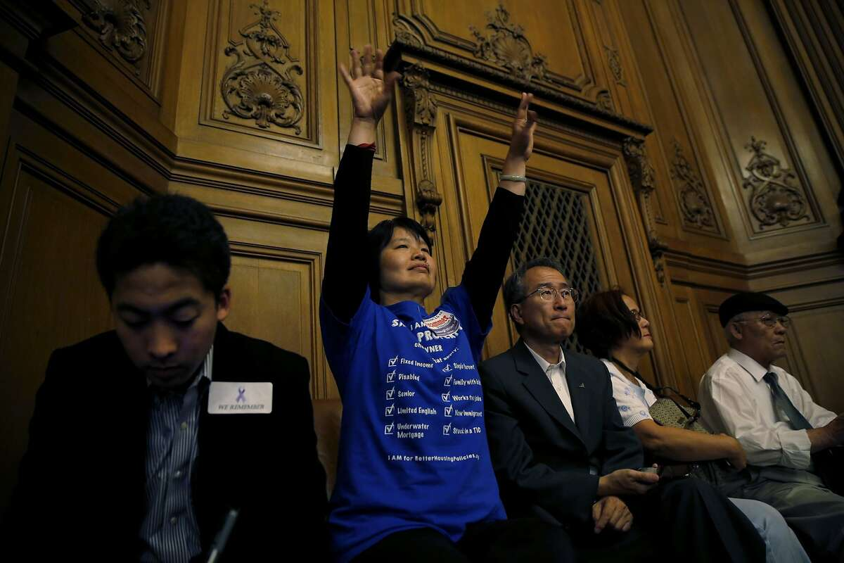 Meina Young raises her hands in support of an objection raised by several supervisors during discussion of eviction protection legislation at a San Francisco Board of Supervisors meeting at City Hall in San Francisco, California, on Tuesday, Sept. 22, 2015.