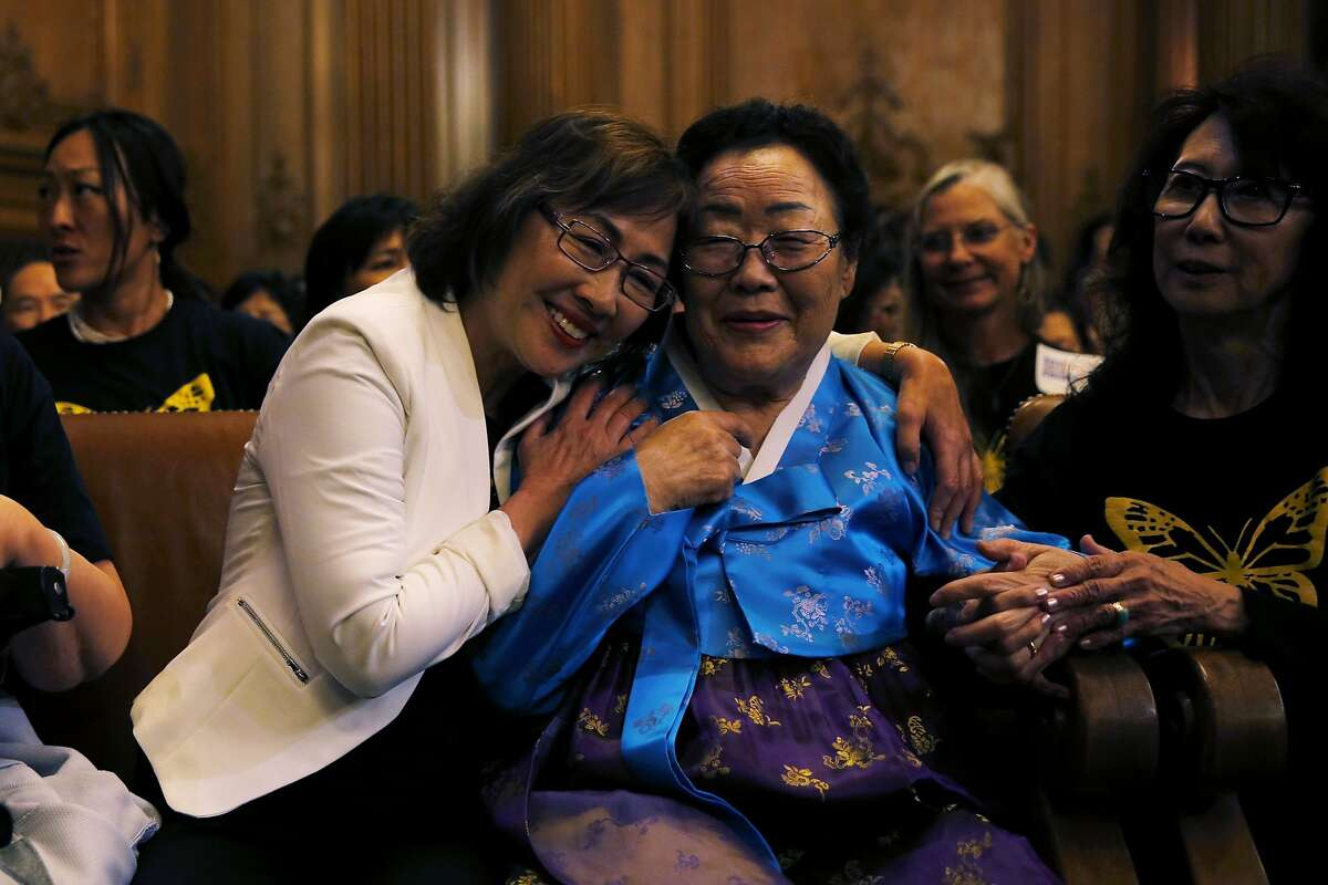 Yong Soo Lee (center), who was enslaved by the Japanese army during the war, receives a hug at a San Francisco Board of Supervisors meeting at City Hall in San Francisco, California, on Tuesday, Sept. 22, 2015.