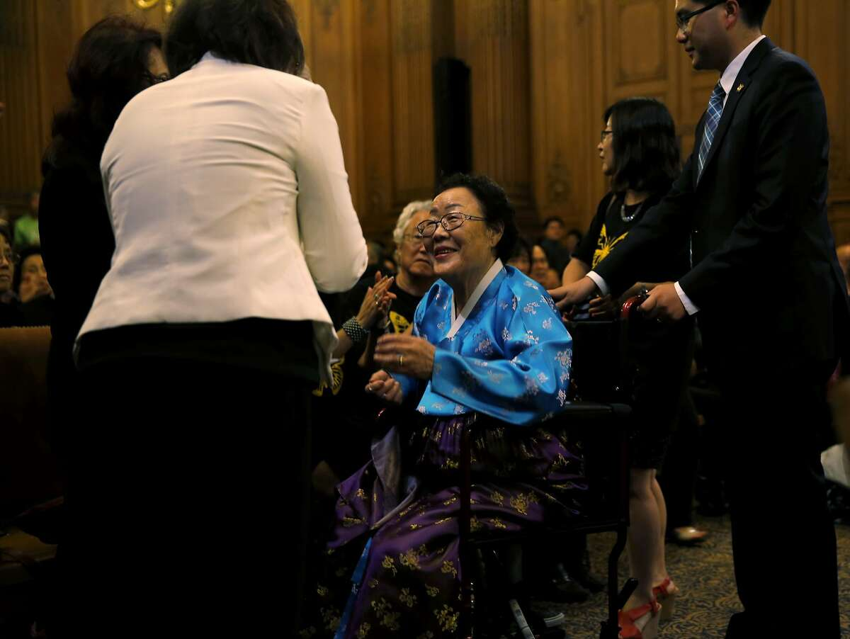 Yong Soo Lee (center), who was enslaved by the Japanese army during the war, is greeted at a San Francisco Board of Supervisors meeting at City Hall in San Francisco, California, on Tuesday, Sept. 22, 2015.