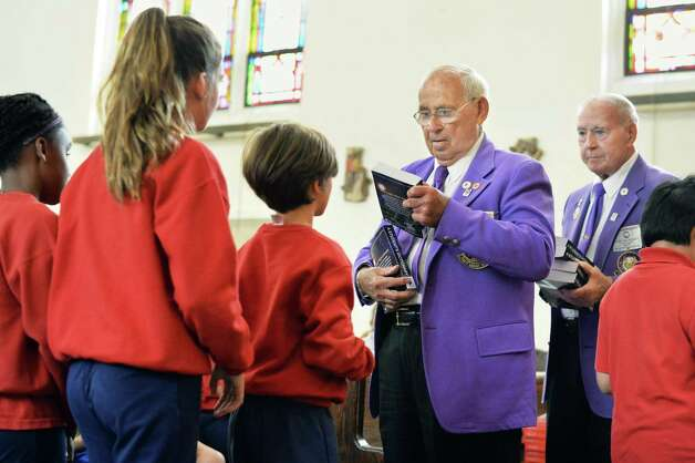 BPO ELKS Troy Lodge #141 members Walter Hughes and Bud McGrath, right, present the gift of a dictionary to each third grader at Sacred Heart School Tuesday Sept. 22, 2015 in Troy, NY.  (John Carl D'Annibale / Times Union) Photo: John Carl D'Annibale / 00033447A
