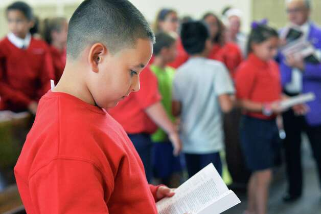 Sacred Heart School third grader Juleon Talavera thumbs through the dictionary given him by BPO ELKS Troy Lodge #141 members at the school Tuesday Sept. 22, 2015 in Troy, NY.  (John Carl D'Annibale / Times Union) Photo: John Carl D'Annibale / 00033447A
