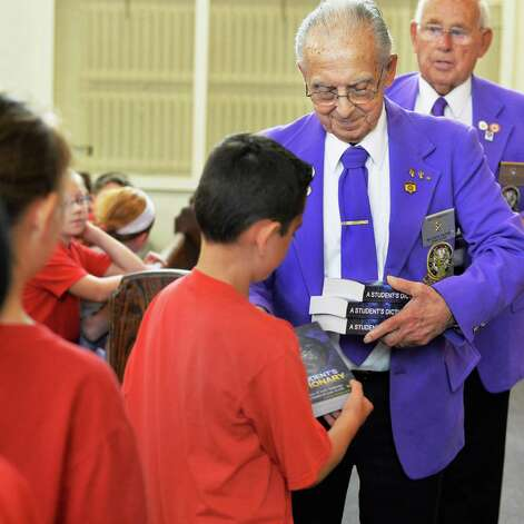 BPO ELKS Troy Lodge #141 members Mike Paone and Walter Hughes, right,  present the gift of a dictionary to each third grader at Sacred Heart School Tuesday Sept. 22, 2015 in Troy, NY.  (John Carl D'Annibale / Times Union) Photo: John Carl D'Annibale / 00033447A
