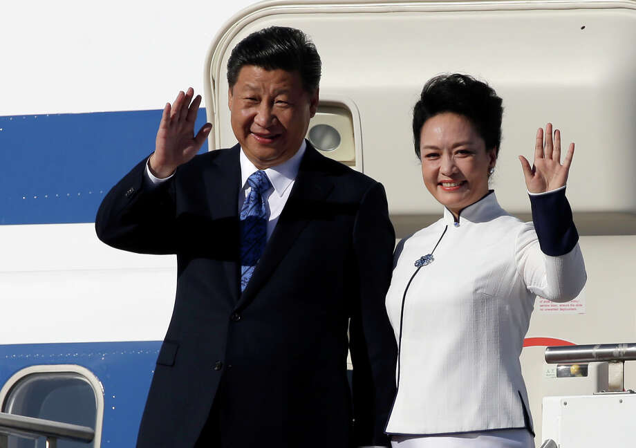 Chinese President Xi Jinping, left, and his wife Peng Liyuan wave upon arrival Tuesday, Sept. 22, 2015, at Boeing Field in Everett, Wash. Xi is spending three days in Seattle before traveling to Washington, D.C., for a White House state dinner on Friday. (AP Photo/Elaine Thompson) Photo: Elaine Thompson, STF / Associated Press / AP