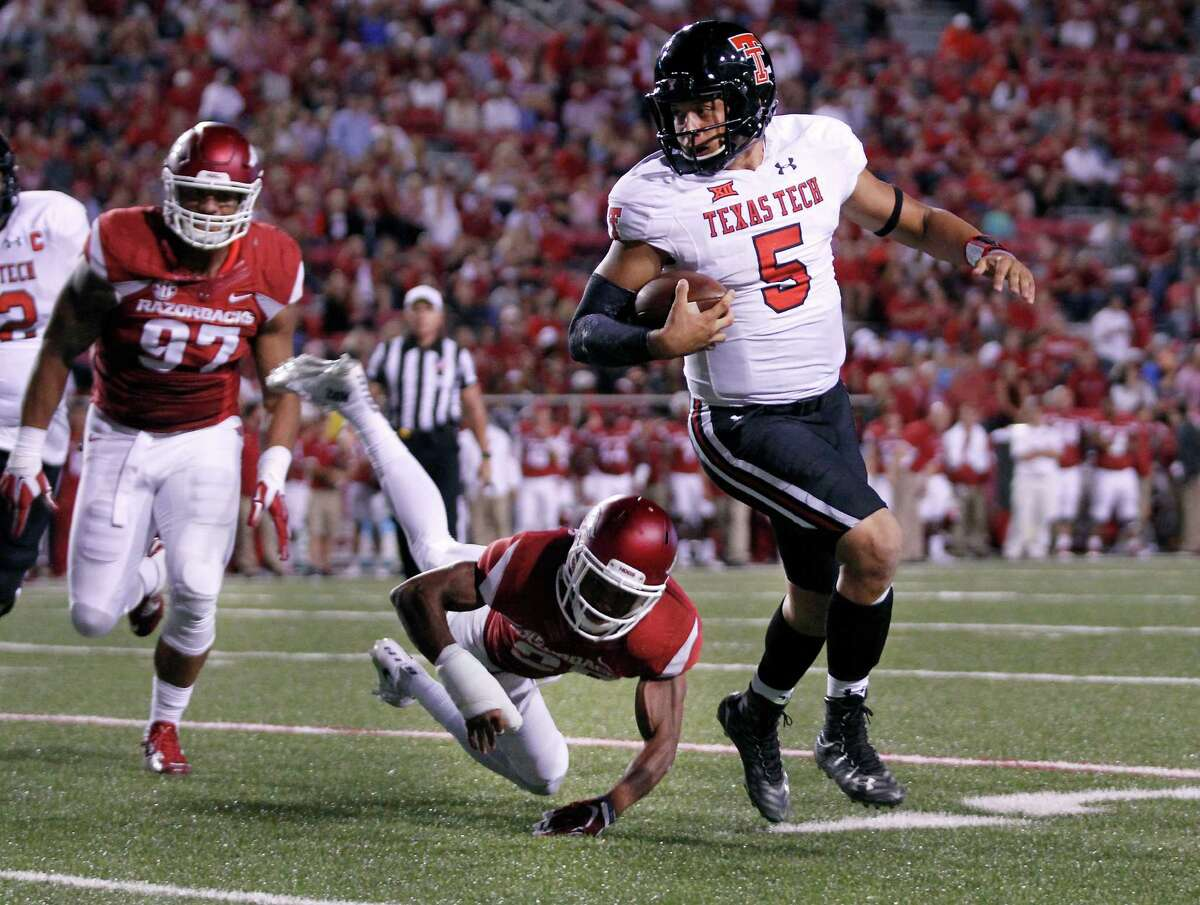 Arkansas defensive lineman Tevin Beanum (97) and defensive back Jared Collins chase Texas Tech quarterback Patrick Mahomes II during the second half of an NCAA college football game Saturday, Sept. 19, 2015, in Fayetteville, Ark. Texas Tech beat Arkansas 35-24.